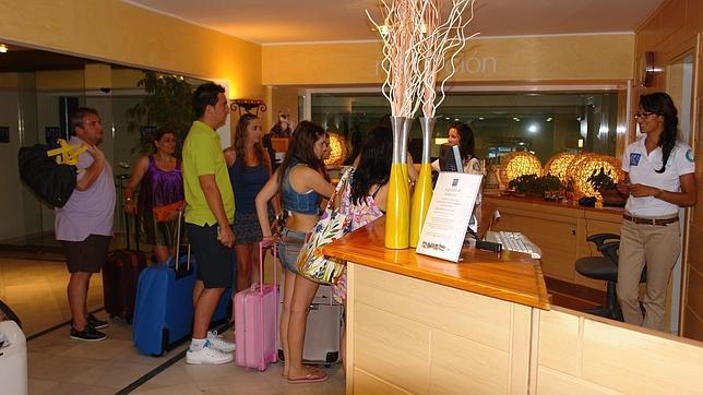 Un nutrido grupo de personas entrando en un hotel de for Hoteles con habitaciones para cinco personas