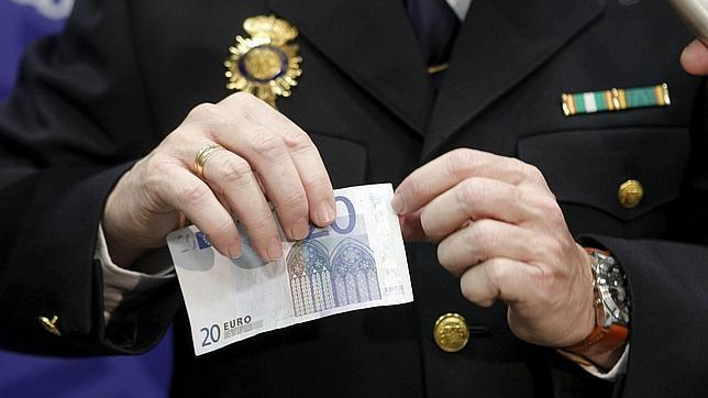 Un policía, detectando un billete de euro falso