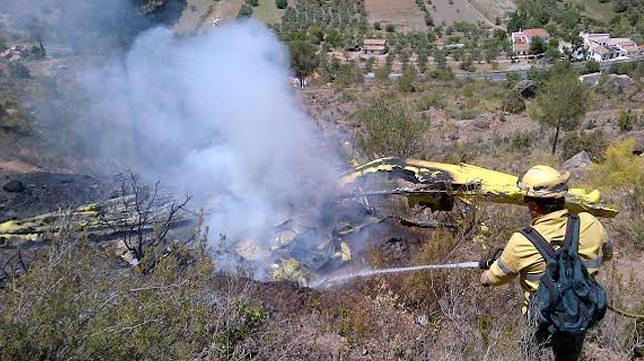 Un compañero de la fallecida rocía los restos del avión con agua