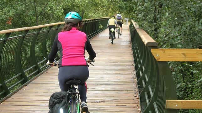 Ciclistas cruzando el Rivera del Huéznar por uno de los puentes de la vía verde