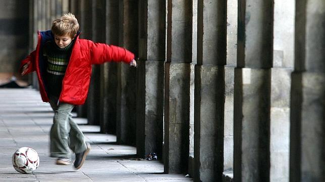 Un niño juega con su pelota en la calle