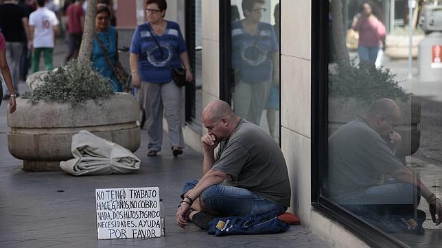 Un indigente pide dinero en una calle de Sevilla