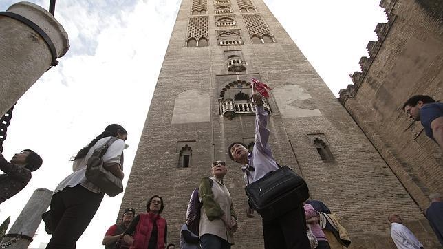 Turistas a los pies de la Giralda de Sevilla