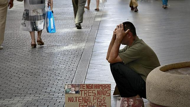 Un indigente pide limosnas en una calle de Sevilla