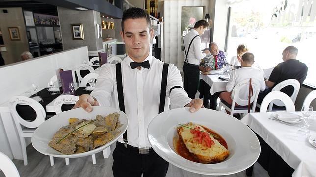 Un camarero La Mafia enseña algunos de los platos que ofrece el restaurante en Córdoba