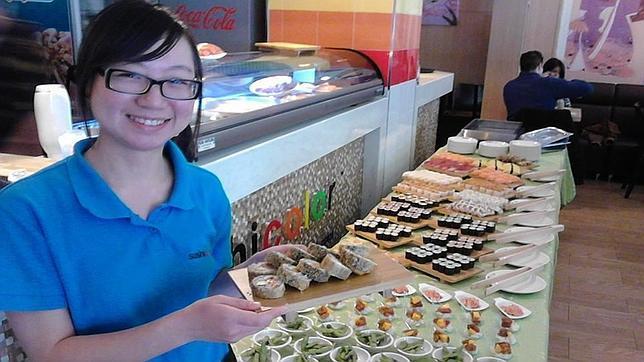 Una empleada de Sushicolor muestra una bandeja del buffet