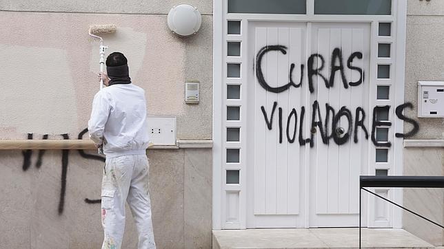 Un operario retira las pintadas que aparecieron en la iglesia al destaparse el caso