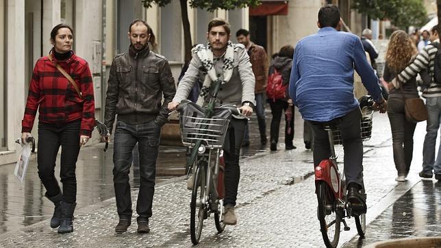 Varios ciclistas por una zona peatonal