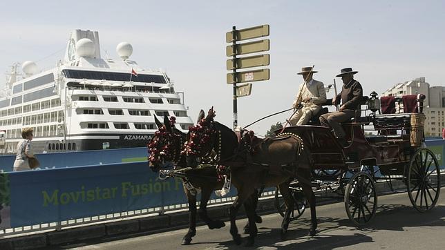 Un coche de caballos cruza el Puente de Los Remedios, junto al buque