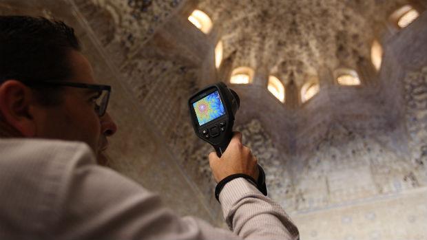 Un investigador toma muestras bajo un techo de mocárabes de la Alhambra