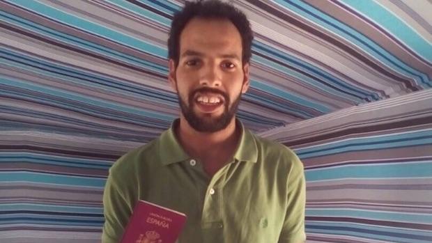 Azman con su pasaporte en una foto enviada a su familia de acogida