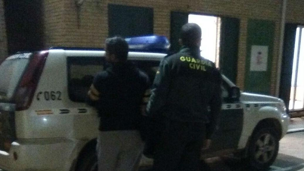 Un agente de la Guardia Civil lleva al presunto agresor hacia el coche patrulla.