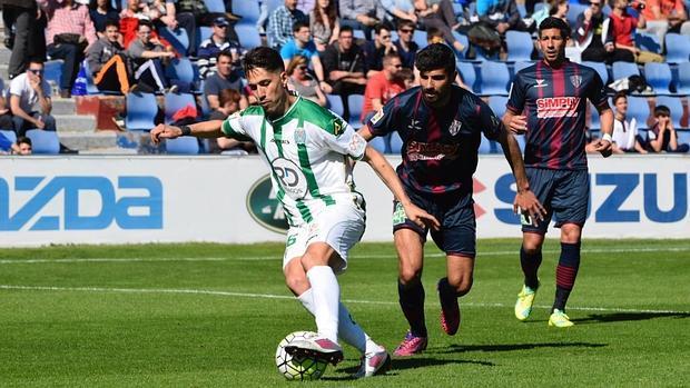 Fidel controla el balón ante la mirada de dos jugadores del Huesca