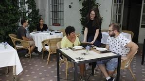 Una joven camarera atiende una mesa en un restaurante de la capital