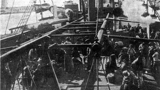 """Emigrantes sobre la cubierta del vapor """"Heliópolis"""", en el Puerto de Málaga. Al fondo se observa la Farola"""