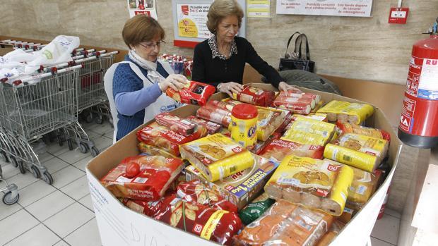 Dos voluntarias de Banco de Alimentos junto a un contenedor de colecta