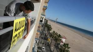 Un propetario de un piso coloca un cartel de alquiler