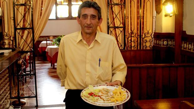 Un camarero del Timón de Cabra enseña su plato estrella: el calamar a la plancha relleno de bacón