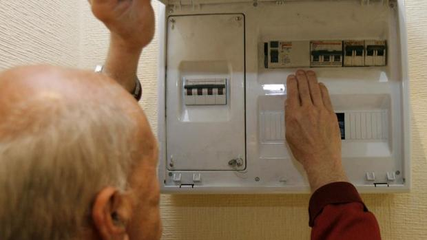 Un hombre manipula un contador eléctrico