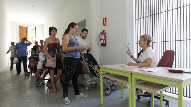 Varias personas se informan en el centro cívico de Lepanto en 2015 de un plan de empleo autonómico