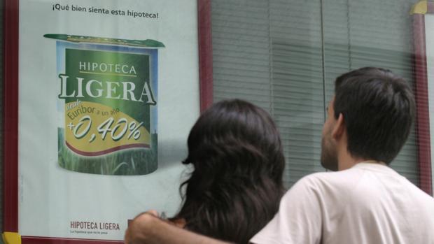 Una pareja mira una publicidad sobre hipotecas en un banco