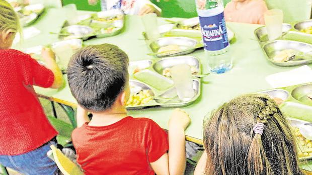 Niños con sus bandejas de almuerzo sobre las mesas del comedor escolar