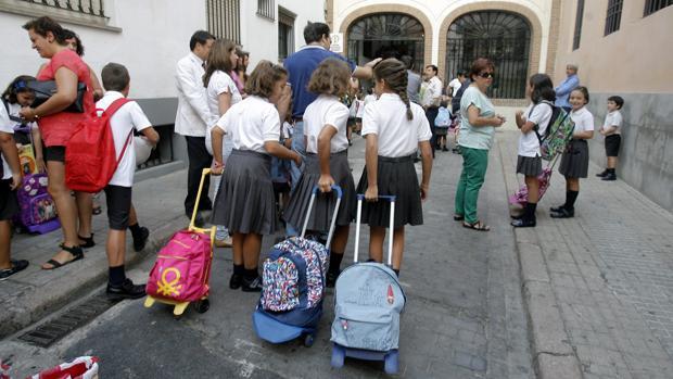 Un grupo de niños llegan al colegio en el primer día de clase