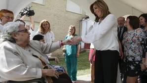Susana Díaz saluda a una mujer durante su visita hoy a las instalaciones de la Fundación Indace