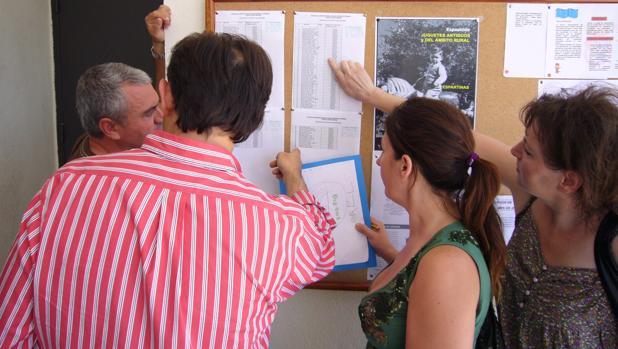 Un grupo de padres consultan unas listas de escolarización en un colegio