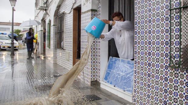 Una vecina evacuando agua del interior de su vivienda con un cubo