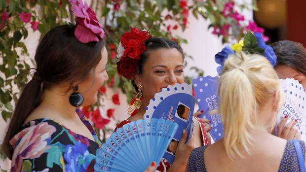 Tres flamencas se abanican en el exterior de una caseta
