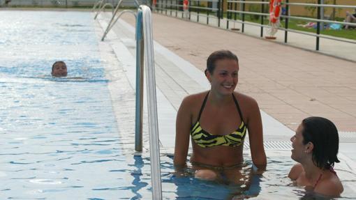 Dos jóvenes charlan en el bordillo de la piscina de Rabanales