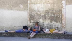 Tres personas descansan en verano en el Patio de los Naranjos de la Mezquita-Catedral de Córdoba