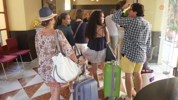 VArias personas hacen cola para registrarse en un hotel de la capital