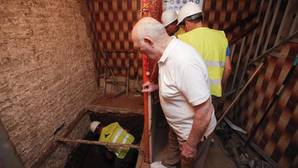 Un vecino observa a los operarios que realizan las obras para instalar el elevador