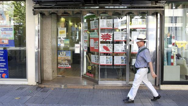 Un viandante camina delante del escaparate de una inmobiliaria
