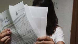 Una chica sostiene una copia de la denuncia y el parte de lesiones