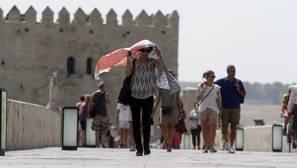 Una turista se cubre el rostro este sábado al atravesar el Puente Romano de Córdoba