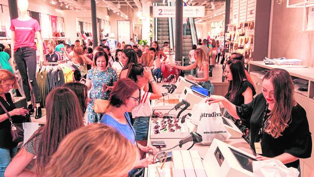 Varias personas en una tienda textil al comienzo de las rebajas