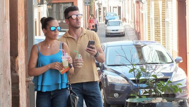 Dos turistas, refresco en mano, recorren Montoro