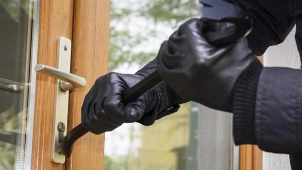 Un ladrón tratando de abrir una puerta