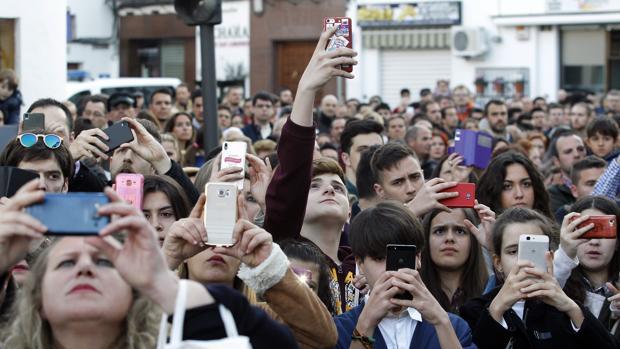 Unas personas toman fotografías al paso de una hermandad