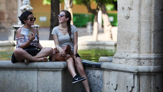 Dos turistas descansan del calor en una fuente.