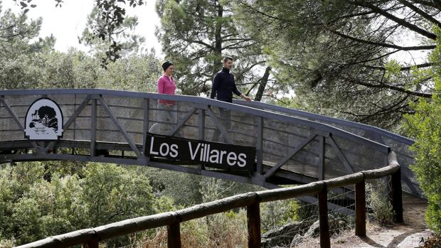 Dos personas pasean sobre un puente en el parque periurbano de Los Villares