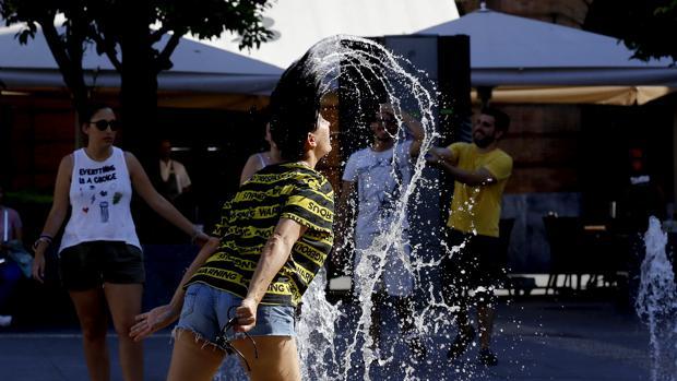Una joven se refesca en una fuente en Córdoba