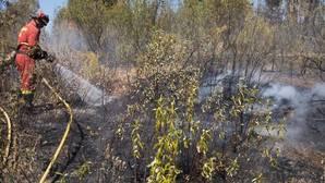 Un bombero del Infoca refresca la zona incendiada