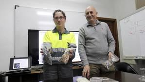 El director de Cosmos y una trabajadora muestran bolsas de biomasa