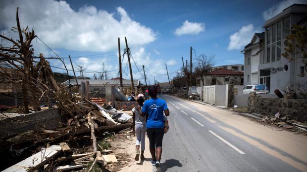 Una mujer y una niña pasean junto a parte de los destrozos provocados por Irma en Saint Martin