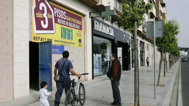Un hombre pasa delante de un anuncio promocionando la venta de pisos nuevos en Tablero Bajo