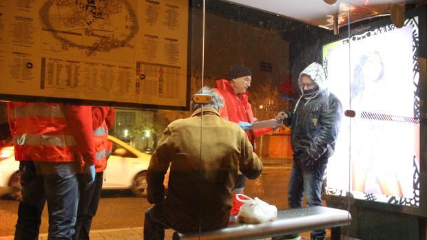 Personal de la Cruz Roja asiste a dos hombres sin recursos en una parada de autobús